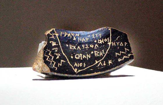 """mappa greca """"di Soleto"""", graffito su ceramica nera, a sinistra TARAS e onde marine"""